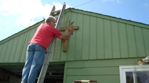 Billie Jo and Craig display the cross on their garage